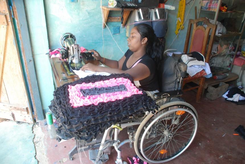 En kvinna sitter i rullstol och syr mattor
