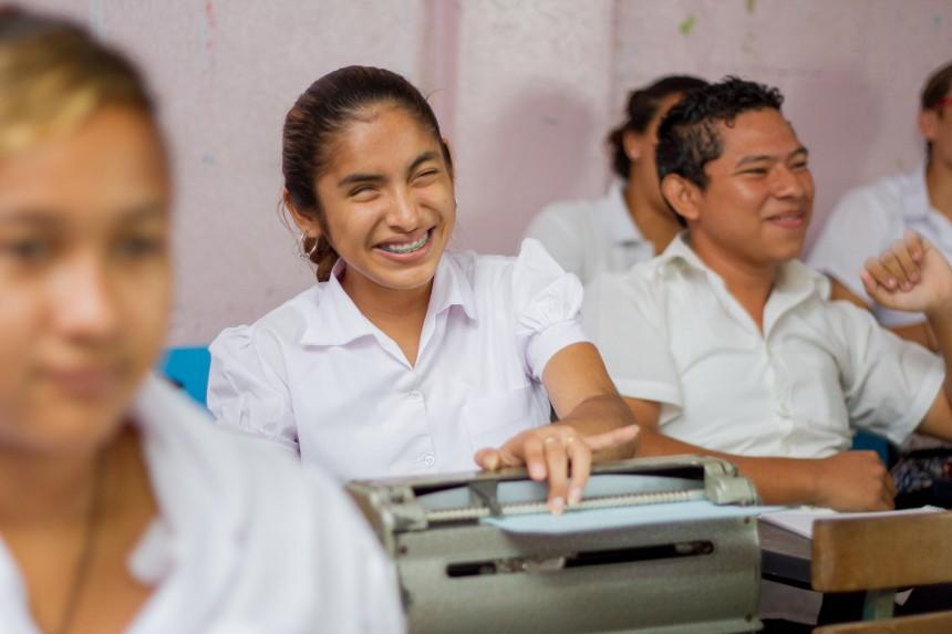 En leende blind flicka sitter vid sin skolbänk och läser på Braille