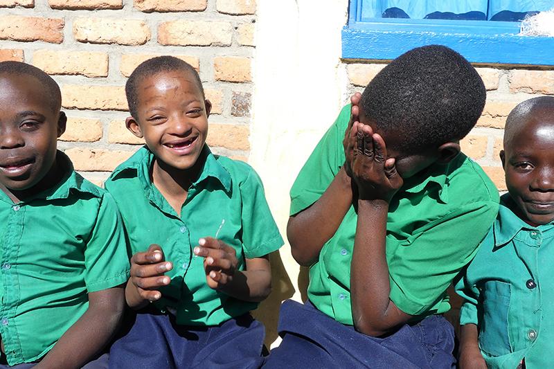 Fyra skolbarn sitter ner vid en vägg och skrattar