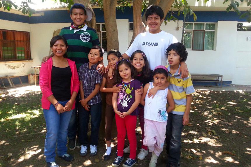 Barn och vuxna som står vid ett träd