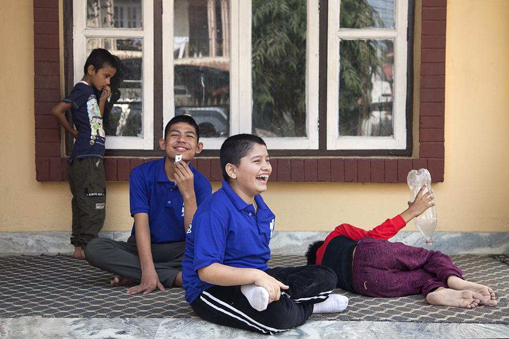 Fyra pojkar sitter på golvet och skrattar.