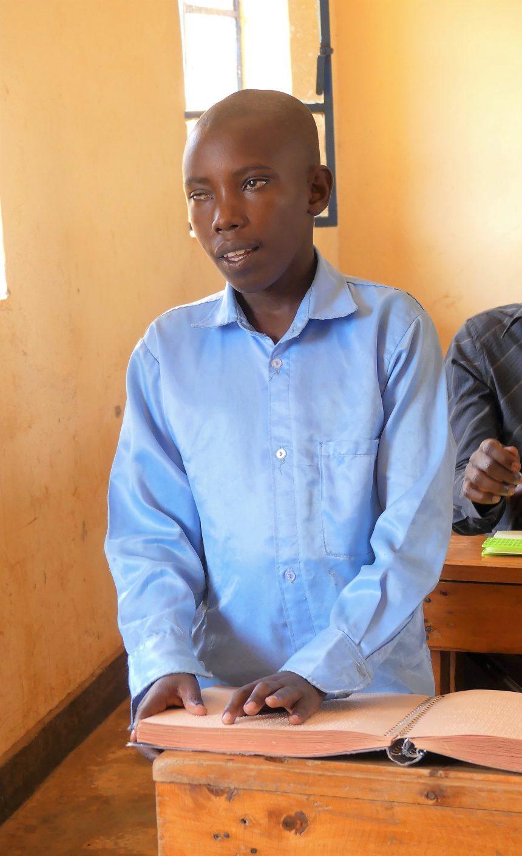 Daniel på Masaka Center, han står vid en skolbänk och läser punktskrift. Han är iklädd en blå skjorta.
