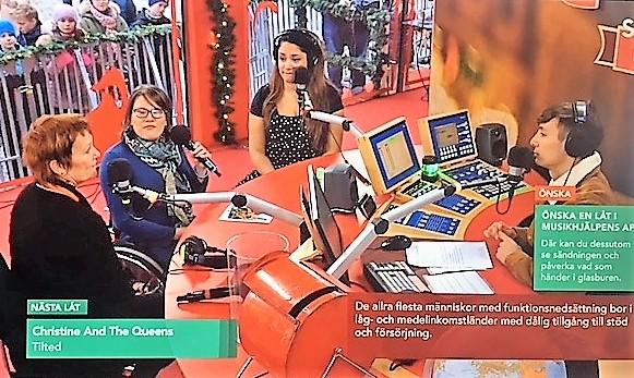 Liiso och Ina intervjuas i en studio. Mikrofoner och dataskärmar. i bakgrunden publik utanför glasburen.