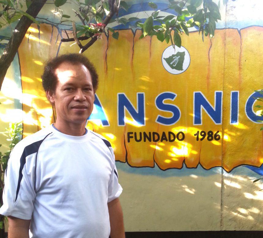 En man står framför en gul vägg