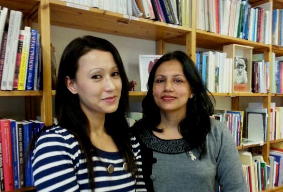 Två kvinnor står framför bokhyllor och ler
