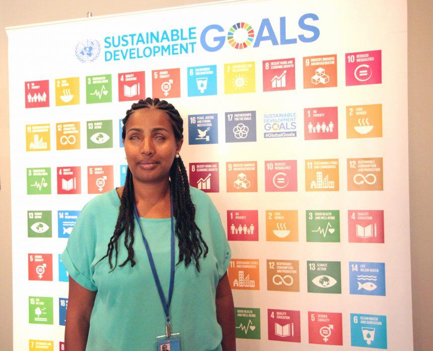 Yetnebersh står framför en tavla med de globala målen