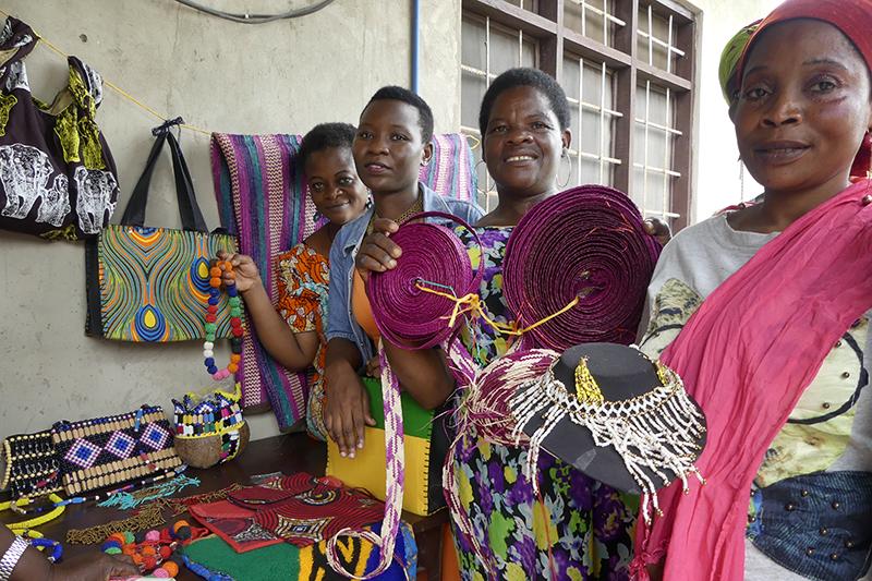 Fyra kvinnor ler och visar upp olika hantverk.