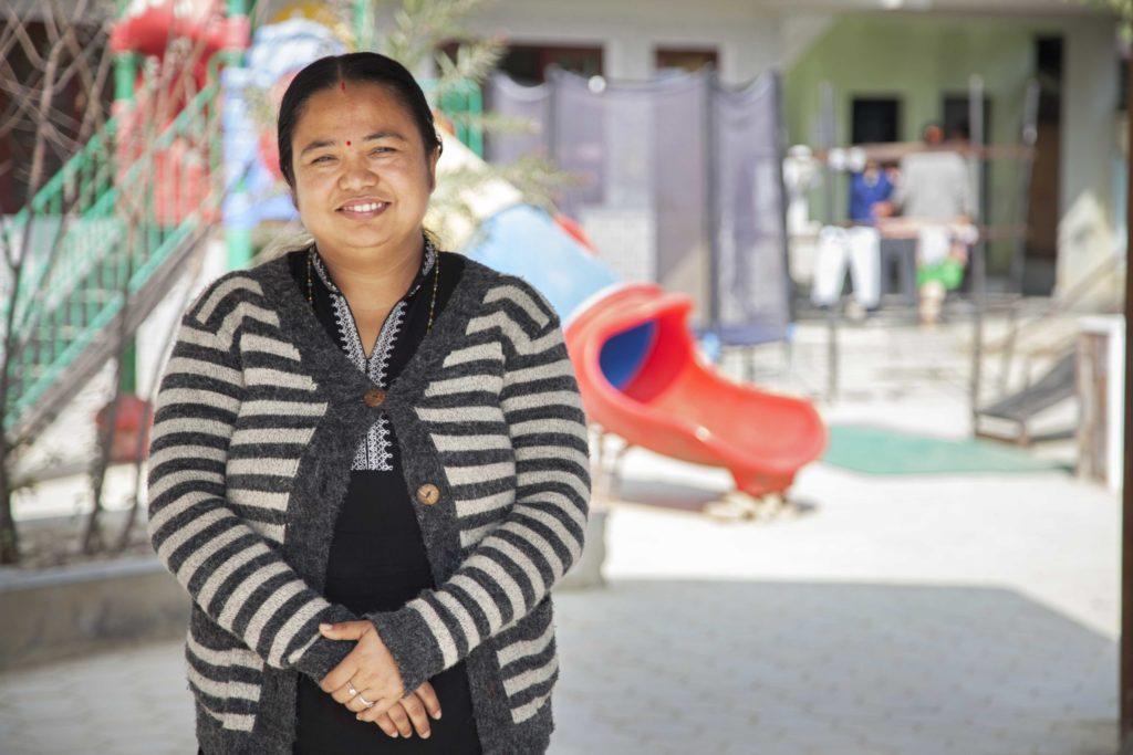 En kvinna står på en skolgård och ler.