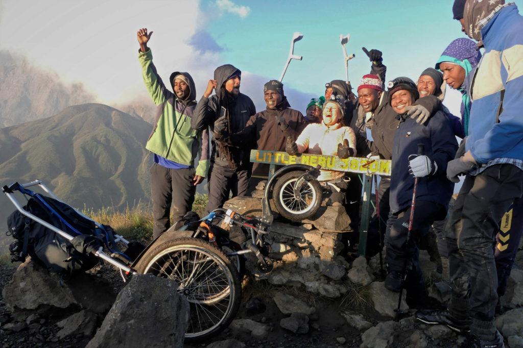 Fler personer står på toppen av ett berg, en kvinna sitter i rullstol.