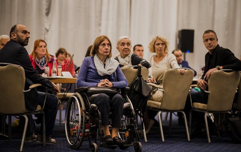 Flera personer sitter ned och lyssnar på en föreläsning. En kvinna sitter i rullstol.