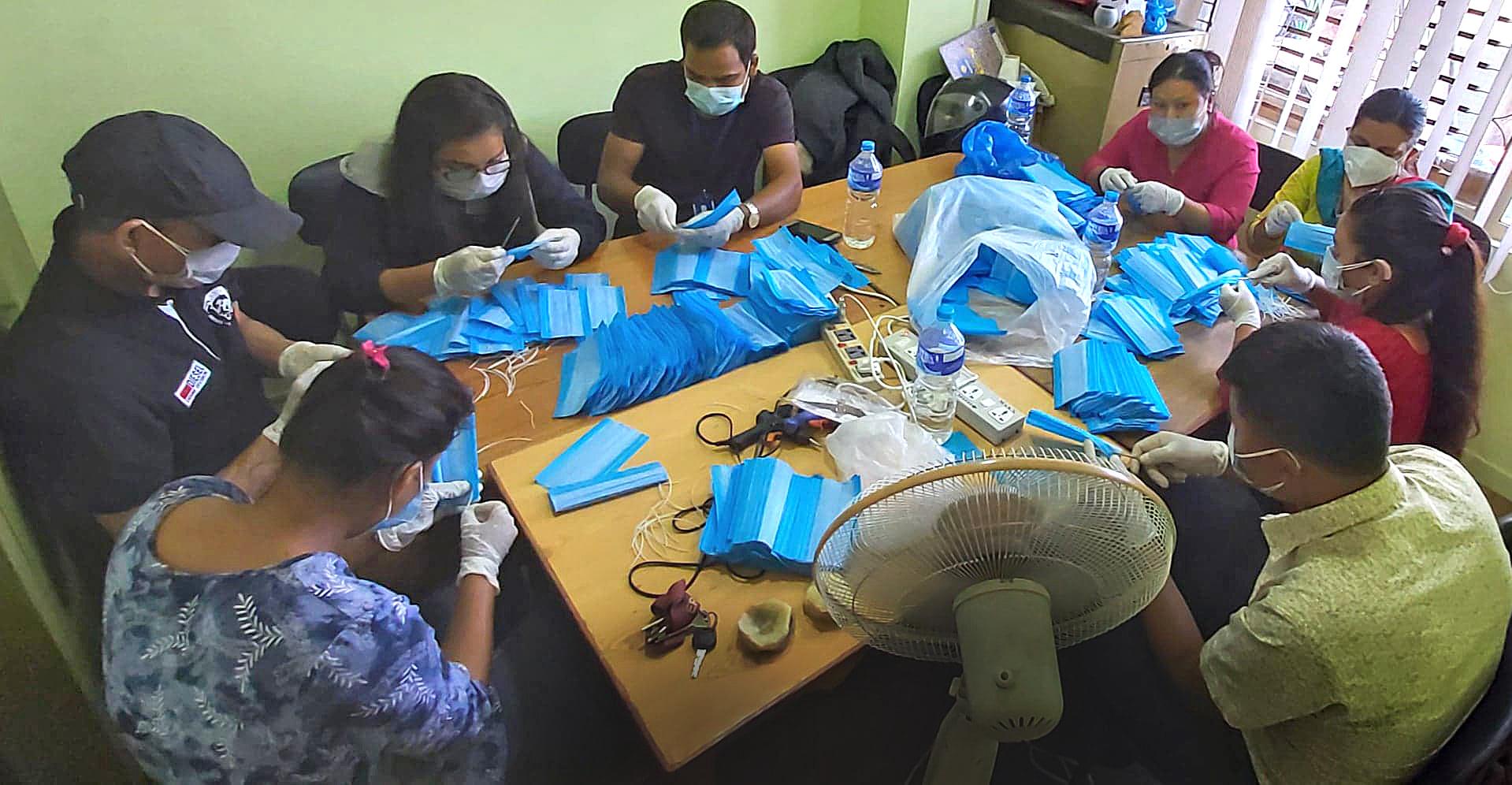 Flera personer sitter kring ett bord och tillverkar ansiktsmasker.