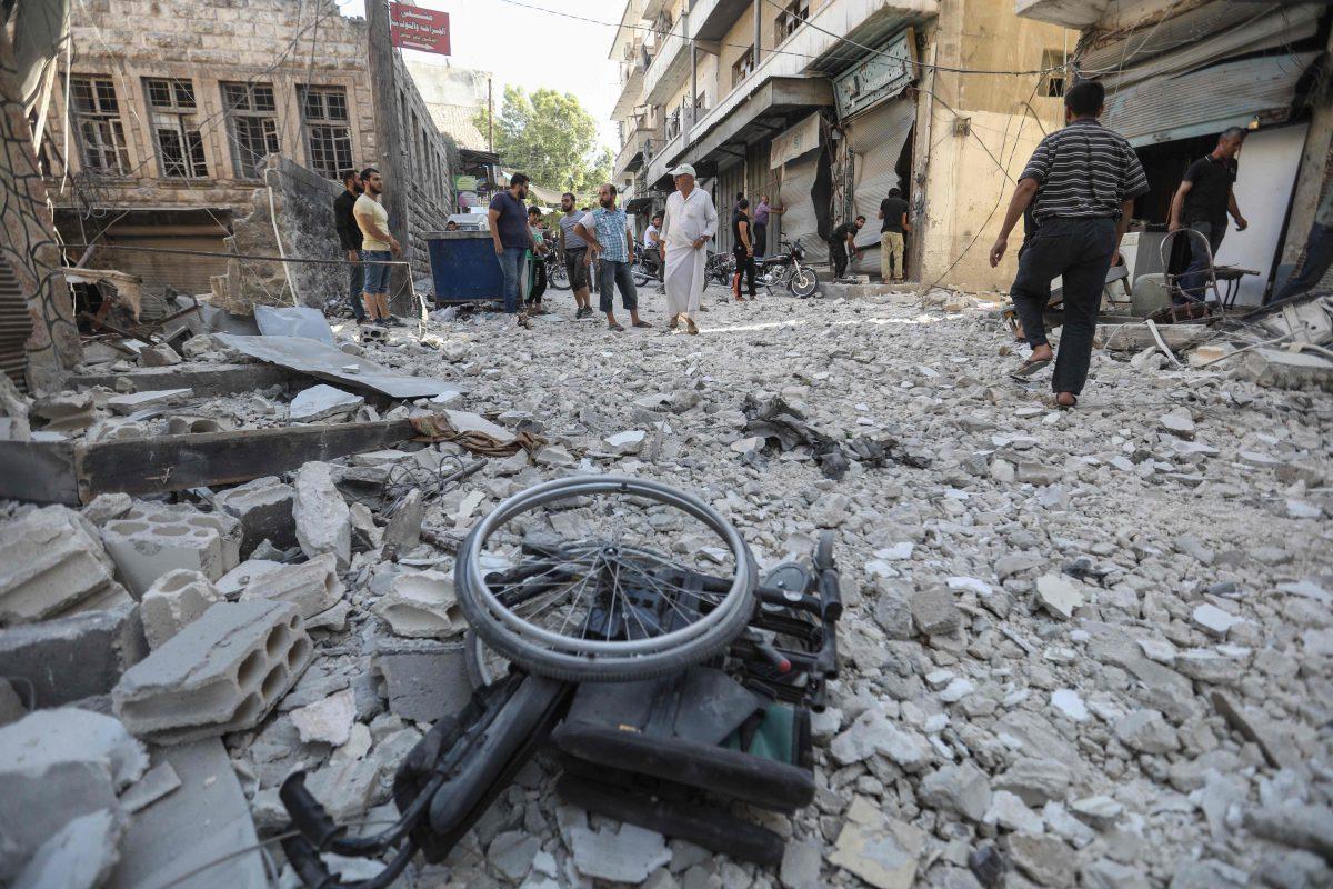 En rullstol ligger bland ruinerna av förstörda byggnader.