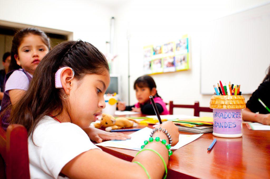 I ett klassrum sitter tre flickor och skriver, en flicka har hörapparat.