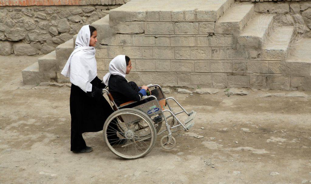 En flicka kör en annan flicka i rullstol.