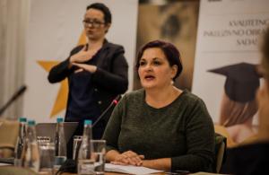 Kvinna med kort brunt hår sitter vid en mikrofon och pratar under ett seminarium