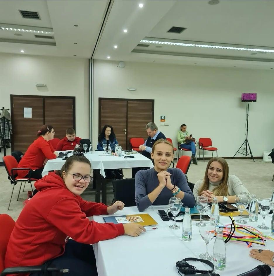 Tre unga kvinnor sitter vid ett bord under workshop i Bosnien Hercegovina alla ler in i kameran
