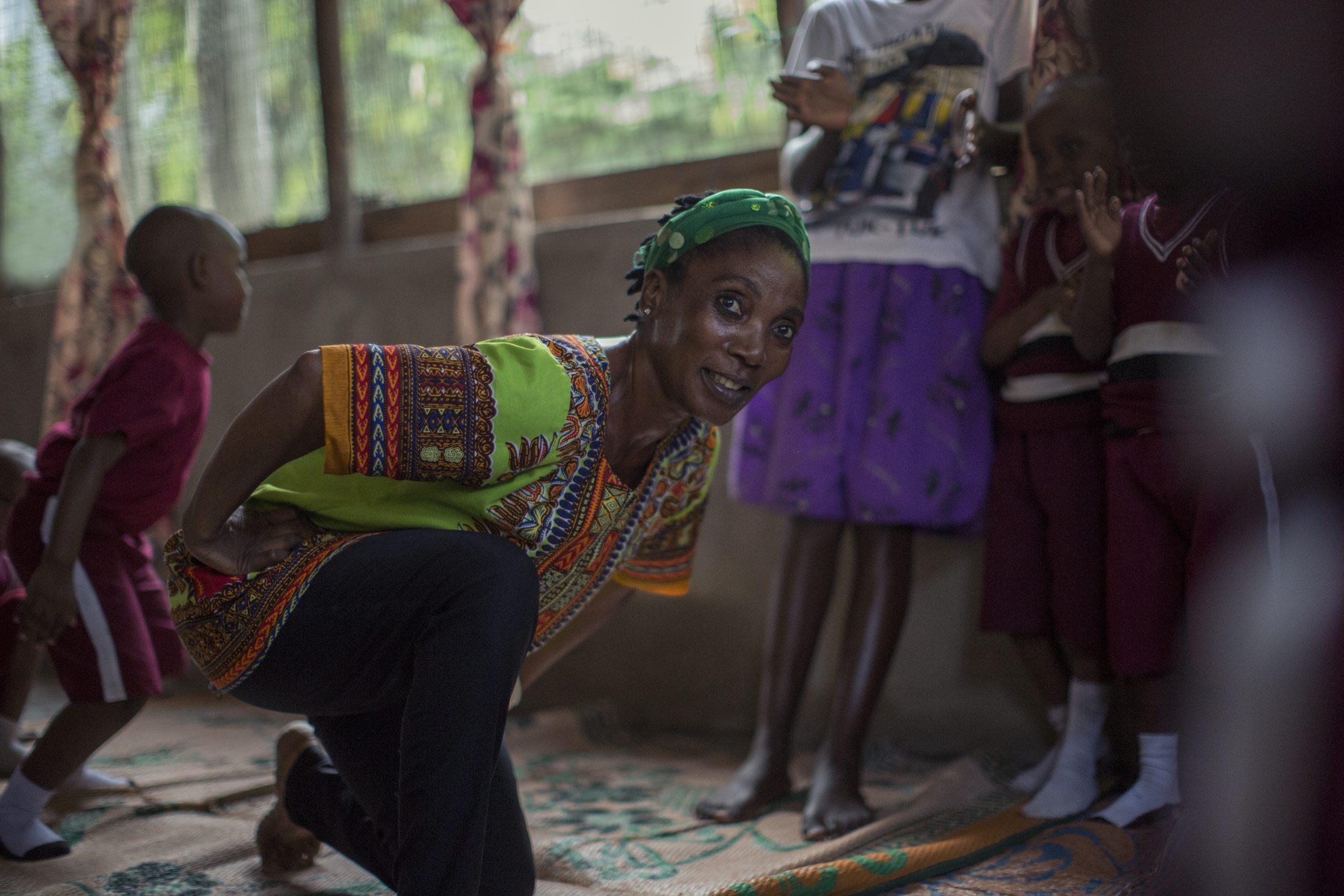 Nindi sitter på huk i en grön tunika och leker med barnen på hennes förskola